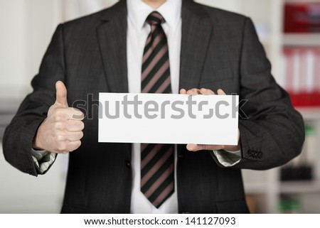 Unrecognized businessman showing thumbs up and holding white envelope - stock photo