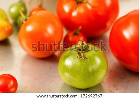 Unripe green tomato with ripe red tomatoes as a soft focus background - stock photo