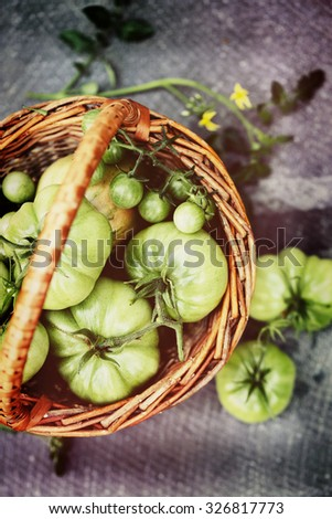 unripe, green tomatoes in a small basket - stock photo