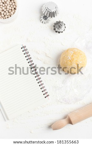 Unrolled and unbaked shortcrust pastry dough with assorted baking tools: rolling pin, ceramic baking beans, mini tart tins and blank recipe book. Taken on a floured white surface, directly from above. - stock photo