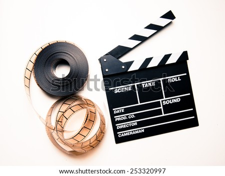 Unrolled 35mm movie reel and clapper board on right side in vintage color effect - stock photo