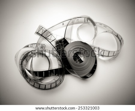 Unrolled 35mm movie reel in vintage black and white and light effect - stock photo