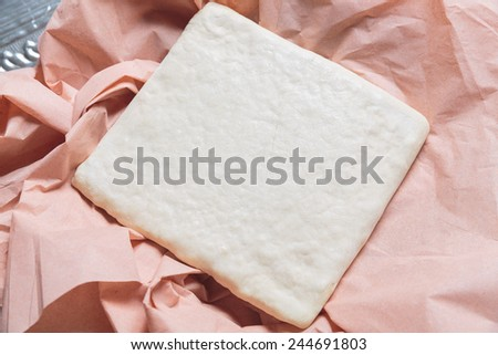 Unrolling dough on paper - stock photo