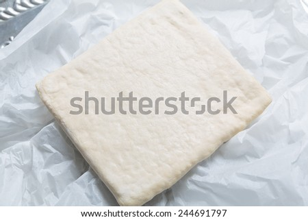Unrolling dough unpacked on paper - stock photo