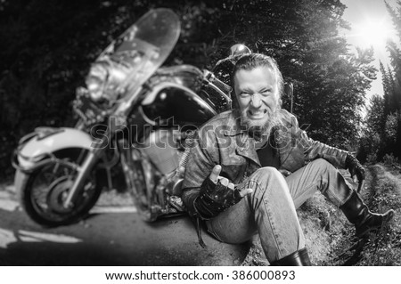 Unshaven male biker in leather jacket and jeans sitting on road near motorcycle and giving the devil horns gesture and smiling. Horizontal picture. Tilt shift lens blur effect. Black and white - stock photo