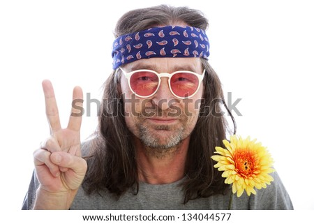Unshaven male hippie with long shoulder length hair wearing a headband, yellow flower and rose coloured glasses making a peace sign with his fingers, head and shoulders portrait isolated on white - stock photo