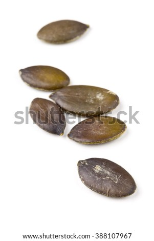 Unshelled pumpkin seeds macro with selectve focus over white background - stock photo