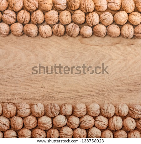 Unshelled walnuts lying on desk can use as background. On the board texture. - stock photo