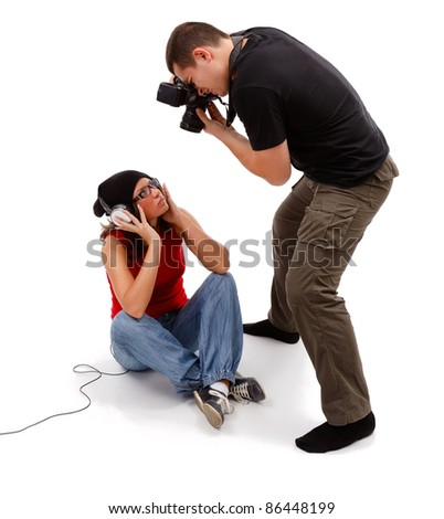 Unshod photographer taking picture from above of sitting female model with headphones and glasses - stock photo