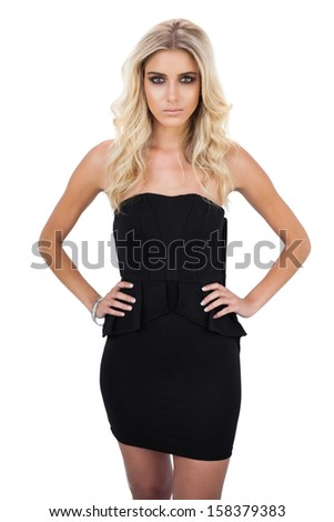 Unsmiling blonde model in black dress posing hands on the hips on white background - stock photo