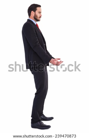 Unsmiling businessman holding something with his hands on white background - stock photo