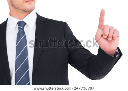 Unsmiling businessman pointing his finger on white background - stock photo