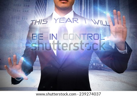Unsmiling businessman touching against urban projection on wall - stock photo