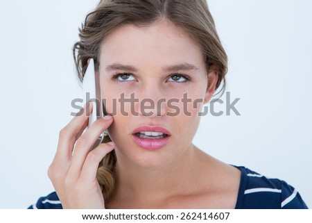 Unsmiling woman calling with her smartphone on white background - stock photo