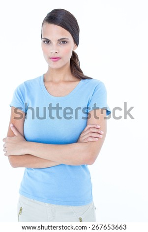 Unsmiling woman looking at camera with arms crossed on white background - stock photo
