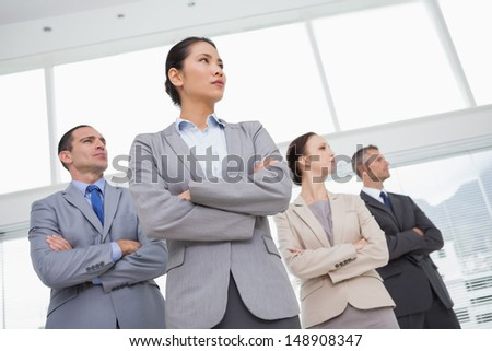 Unsmiling work team posing crossing arms in bright office - stock photo