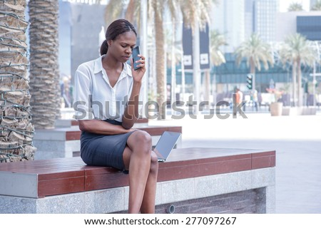 Unsuccessful business. African businesswoman businessman sitting in the street and holding cell phone in hand near the head of Dubai downtown among the skyscrapers and looks forward - stock photo