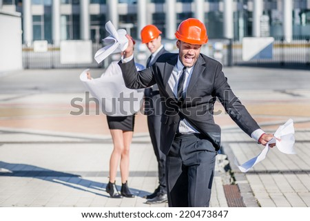 Unsuccessful construction project. Angry architect in the construction helmet breaks his drawing project and shouts while standing on the construction site. - stock photo