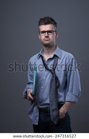 Untidy depressed businessman standing and holding files - stock photo