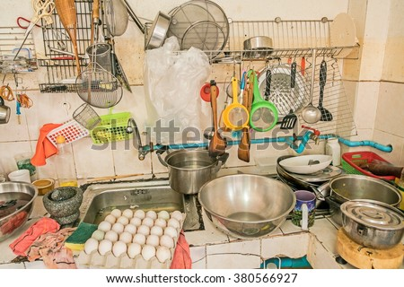 untidy Kitchenware ; Pile of dirty dishes in sink and counter in the kitchen  - stock photo