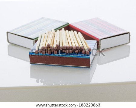 Unused matches with brown head screw in the box and other matchboxes on white background with reflexions - stock photo