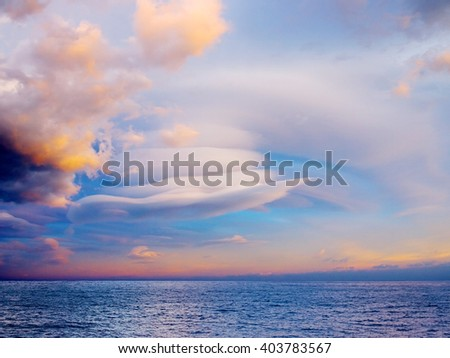 Unusual clouds on the sea. - stock photo
