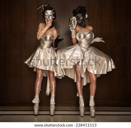 unusual girls with painted faces and masks in hands - stock photo