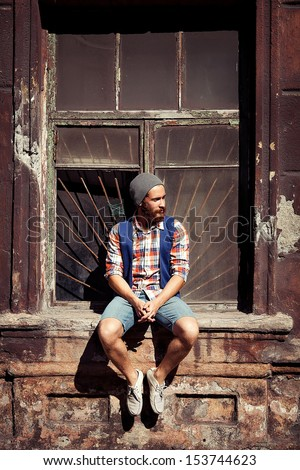 unusual man with beard posing outside - stock photo