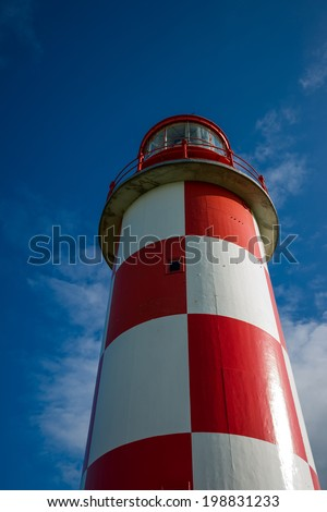 Unusual perspective image of a towering red and white lighthouse standing against a rich, deep blue sky. - stock photo