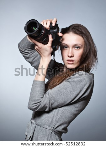 Unusual portrait of beautiful female photographer shooting - stock photo