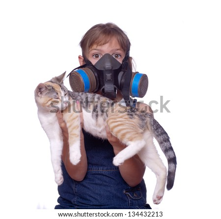 Unusual shot of a kid dealing with pet allergies by wearing a gasmask while holding her cat - stock photo