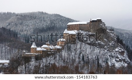 Unusual view of famous Orava Castle in winter after strong snow storm. This panoramic view shows all buildings of Orava Castle as a whole, including Lower, Middle, and Upper castle. - stock photo