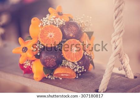 Unusual wedding bouquet for the bride of exotic fruits - oranges, mangosteen, lemons, wedding Asian islands, closeup - stock photo