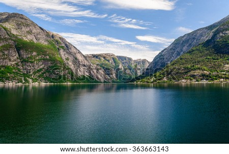 Unusually view on the mountain peaks with the mirror surface of the water and wonderful feather clouds on the sky on background, Norway, Hardangerfjord - stock photo