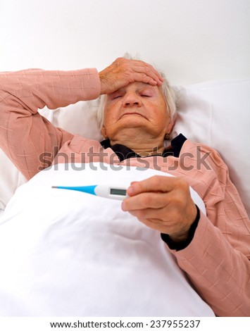 Unwell elderly woman lying in the bed with a thermometer - stock photo