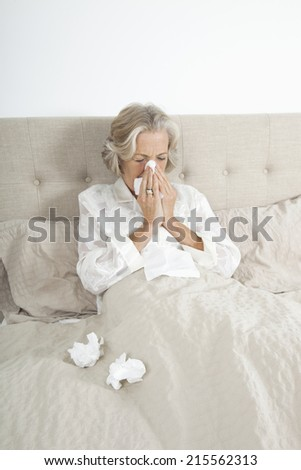 Unwell senior woman blowing nose in bed - stock photo