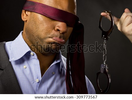 Unwilling male forced by girlfriend to sexual BDSM role playing.  The man is blindfolded and a female hand is holding hand cuffs.  The image depicts sexual fetish with no nudity. - stock photo