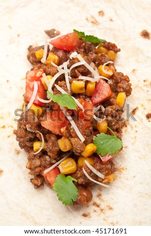 Unwrapped tortilla stuffed with beef chili and cilantro - stock photo