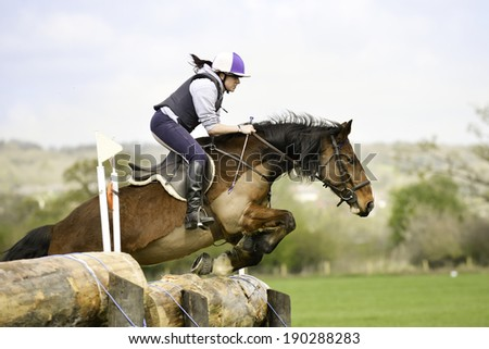 Up and over- young woman and her horse jump huge log in cross country competition in Shropshire countryside. - stock photo