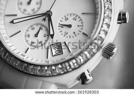 Up close macro black and white photo of white designer watch - stock photo