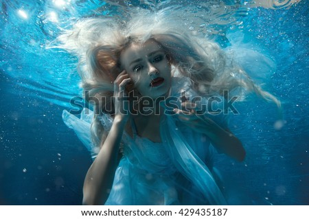 Up portrait of a girl under the water. - stock photo