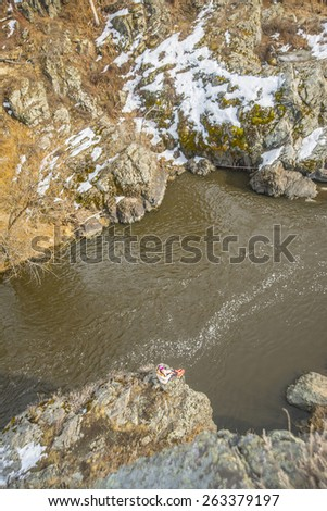 Up view Alone Girl sitting on  edge of mountain rock texture near fast river Little female rest and relax on cold stone Idea concept fast time symbol Foam on dirty spring water Snow lie land - stock photo