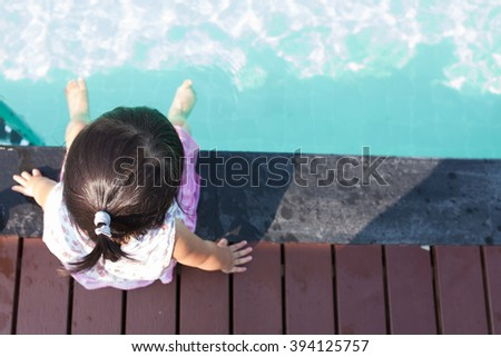 Up view baby sitting near swimming pool. - stock photo