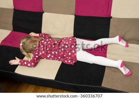 Upbringing problems - little sad girl is lieing on the sofa facedown - stock photo