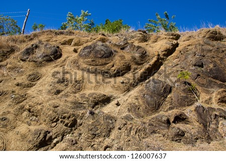 Uplifted pillow lava's outcropping near a road-section (Sierra Madre, Cuba). Pillow basalt forms due to the extrusion of lava under water resulting in characteristic pillow-shaped - stock photo