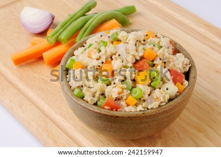 Upma or Uppuma cooked as a thick porridge from dry roasted oat  seasonings of vegetables are often added during the cooking, - stock photo