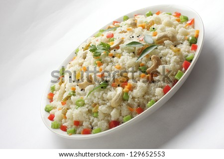 Upma or Uppuma  is a common South Indian breakfast dish, cooked as a thick porridge from dry roasted semolina. seasonings of vegetables are often added during the cooking,  - stock photo