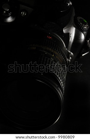 upper angle view of a reflex photo camera in low-key light - stock photo