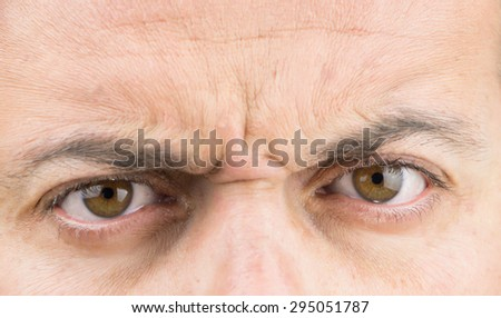 Upper part of males face closeup on angry eyes - stock photo