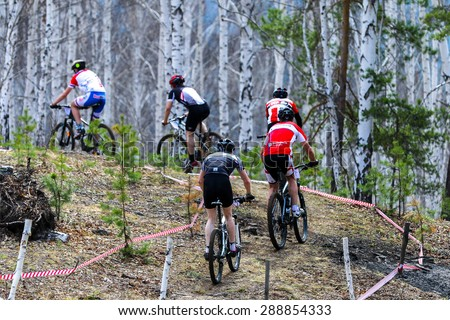 """Upper Ufaley, Russia - May 04, 2015: A mountain biker competes during the race """"Le Tour de Turshavel 2015"""" - stock photo"""